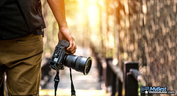 Best website builder for photographers: photographer holding a camera.